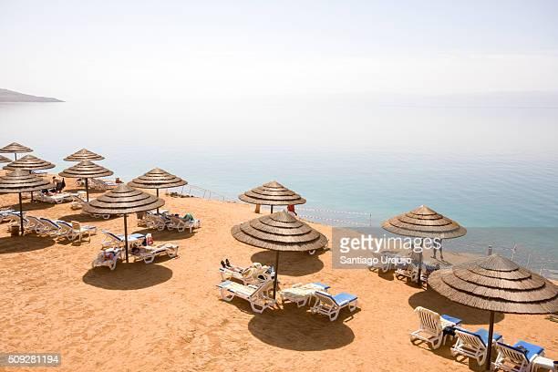 parasols and sun loungers on a beach on the dead sea - amman stockfoto's en -beelden