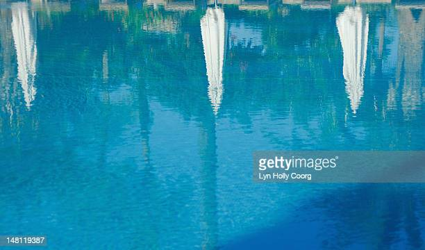 parasols and trees reflected in a swimming pool - lyn holly coorg stock pictures, royalty-free photos & images