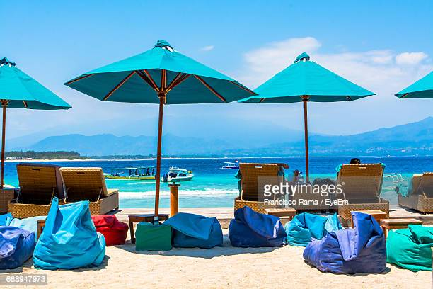 parasols by lounge chairs and bean bags on sand at beach against sky - gili trawangan stock photos and pictures