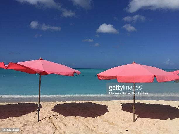 Parasols On Shore At Beach Against Sky