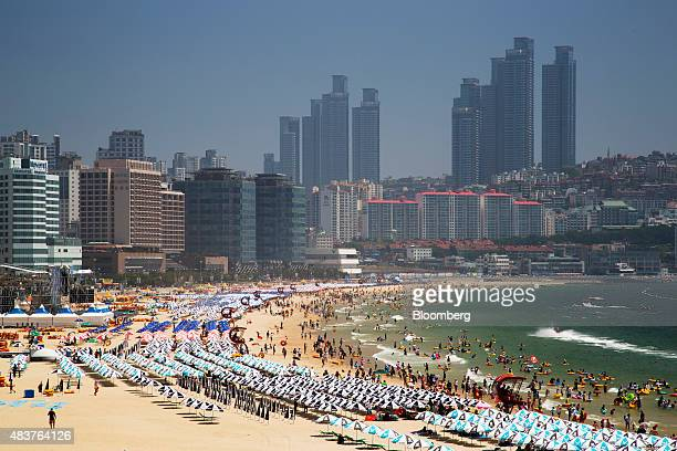 Parasols stand as people swim in the sea at Haeundae beach in Busan South Korea on Friday July 31 2015 South Korea urged its people to put the...