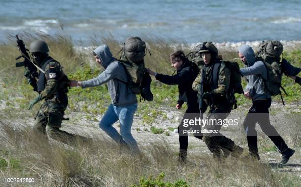 A paratrooper accompanies a group of actors posing as civilians near Waabs Germany 15 May 2017 The exercise 'Red Griffin/Colibri 50' of the Special...