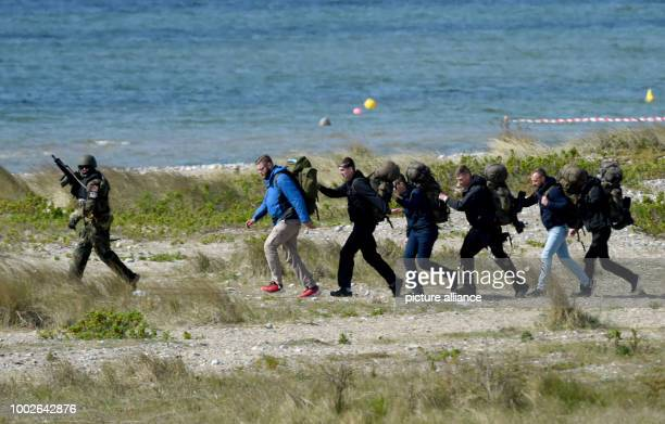 A paratrooper accompanies a group of excellent actors posing as civilians near Waabs Germany 15 May 2017 The exercise Red Griffin/Colibri 50 of the...