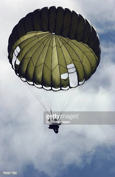 a paratrooper descends through the sky. - paratrooper stock pictures, royalty-free photos & images