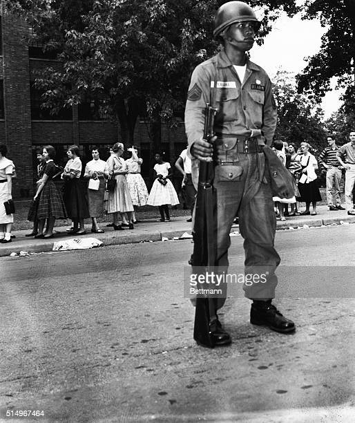 A paratrooper from the 101st Airborne division stands guard outside Little Rock's Central High school here on September 25th as students chat during...