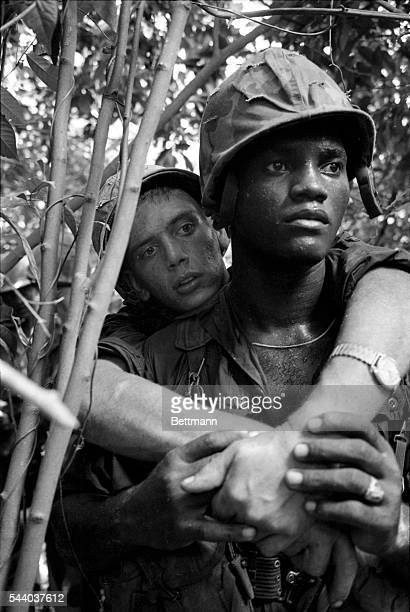 Paratrooper William L Seeley of Portland Oregon is carried piggyback by a buddy after breaking his ankle during an operation in the Viet Cong jungle...
