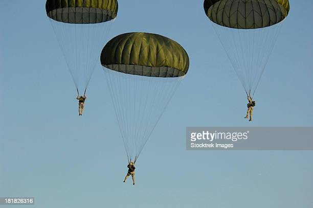Paratroopers descend through the sky.