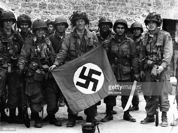 Paratroopers display a Nazi flag captured in an assault on a French village.