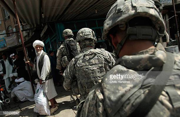 Paratroopers in the 4th Brigade of the US Army's 82nd Airborne Division patrol through a busy market street as a man watches June 26 2010 in downtown...