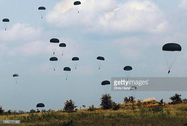 Paratroopers in the First Brigade of the US Army's 82nd Airborne Division parachute float to the ground during a training jump August 6, 2010 at Camp...