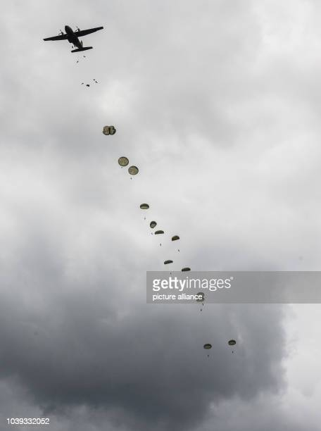 Paratroopers jump out of a Bundeswehr airplane at the German army military training area Oberlausitz in Weisskeissel Germany 30 June 2013 The...