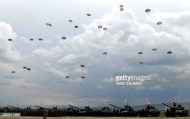 TOPSHOT Paratroopers jump out of a plane during an opening ceremony of the joint military exercise Noble Partner 2016 at the Vaziani training area...