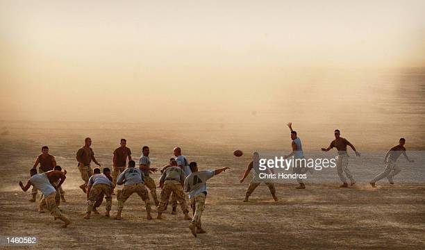 Paratroopers of the 82nd Airborne play touch football on the landing zone of a forward US Army base October 5 2002 in southeastern Afghanistan US...