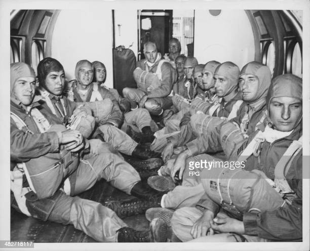 Paratroopers, wearing full field gear and parachutes, in the holding bay of a transport plane during World War Two, circa 1941-1945.