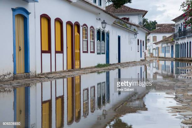 A flooded and reflective view of colorful colonial houses.