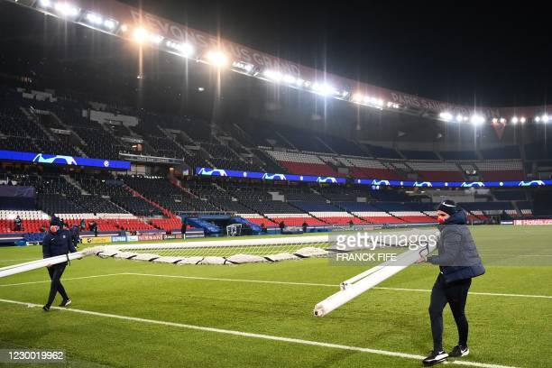 Parc des Princes stadium employees remove a goal in Paris on December 8, 2020 after suspended UEFA Champions League group H football match between...