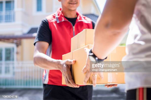parcel delivery man of a package through a service and customer hand accepting a delivery of boxes from delivery man. - delivery person stock pictures, royalty-free photos & images