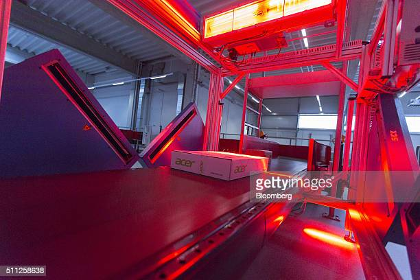 A parcel is illuminated by red sensor light beams as it passes through a scanning machine manufactured by Sick AG at a mechanized postal delivery...