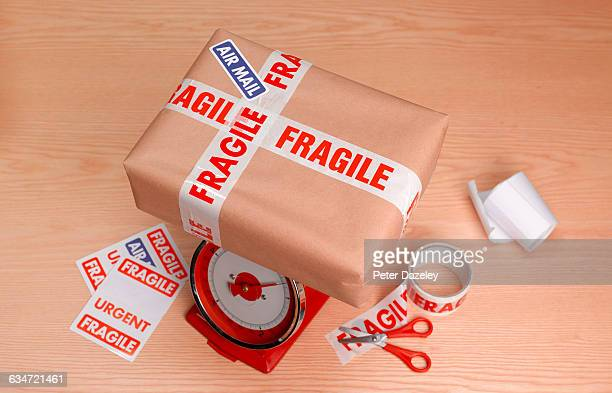 parcel to post on scales - fragile sign stock pictures, royalty-free photos & images
