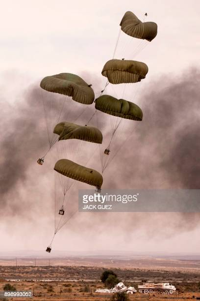 Parcels dropped from an Israeli C130 Hercules fall to the ground during the graduation ceremony of Israeli air force pilots at the Hatzerim Israeli...