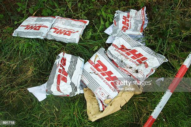 Parcels lie in the grass near the wreckage of a DHL Boeing 757 cargo plane July 2, 2002 in a forest near the town of Taisersdorf, Germany. The...