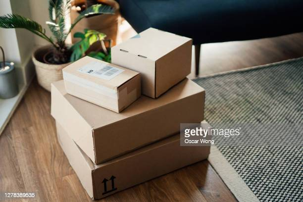 parcels on floor in a living room - cardboard box stock pictures, royalty-free photos & images