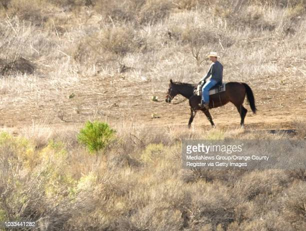 Parched landscape minus a spot of green envelopes a horseback rider at Peters Canyon Regional Park in Orange on Monday Volunteers were stationed...