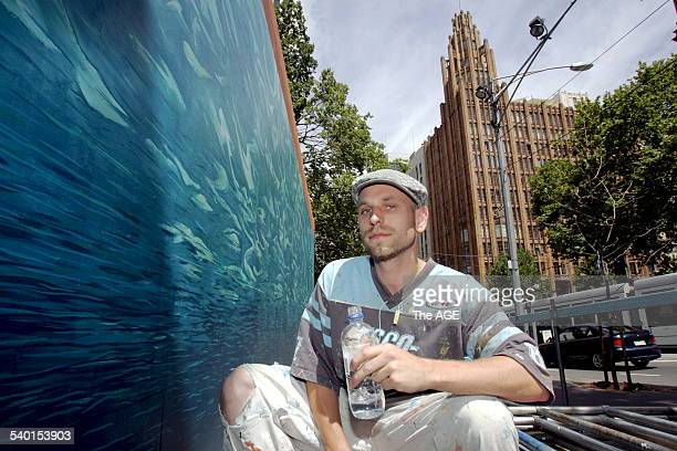 Parched Melbourne artist Ash Keating enjoys a drink after completing the second of 15 changes to his artwork -- having painted a version of Melbourne...