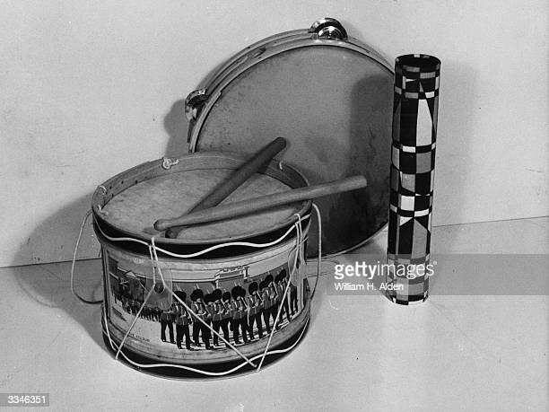 A parchment sided drum decorated with an image of the Trooping of the Colour ceremony complete with drumsticks a tambourine and a kaleidoscope on...