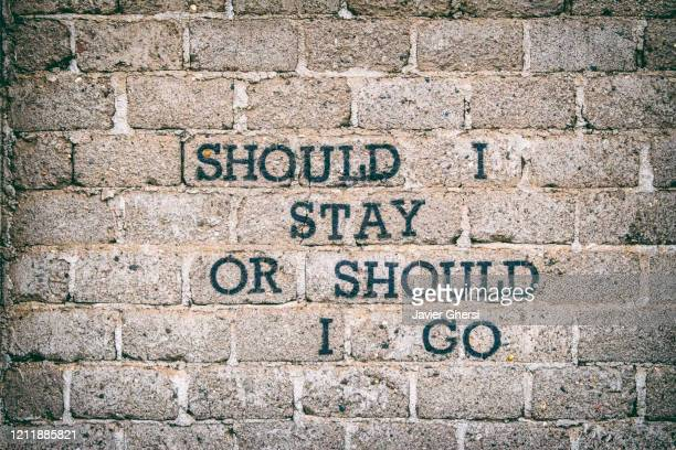 "pared de ladrillos con frase: ""should i stay or should i go"" - the clash. (diseño propio). - punk music stock pictures, royalty-free photos & images"