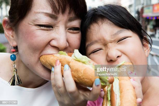 Parent and child eating hot dogs