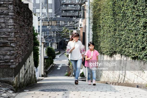 Parent and child eating ice while walking