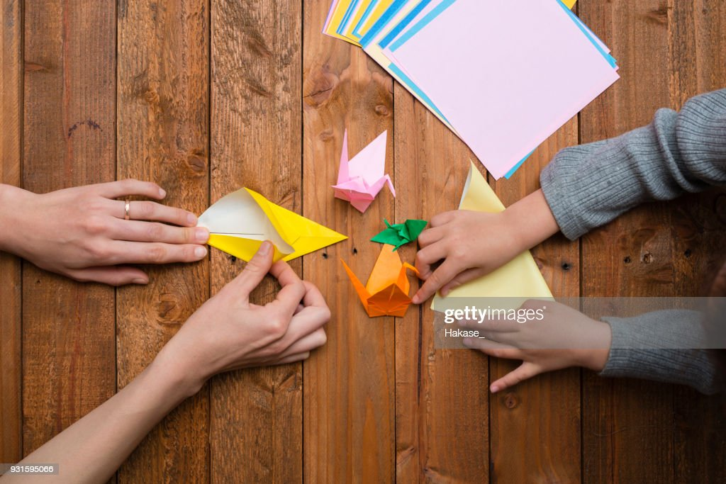Parent and child hand playing with origami : Stock Photo