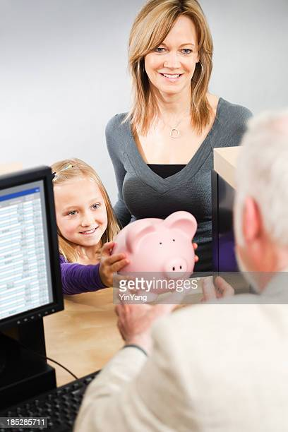 Parent and Child Taking Saving to Retail Bank Teller Counter