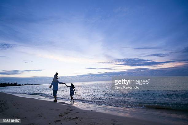 Parent and child walking the beach