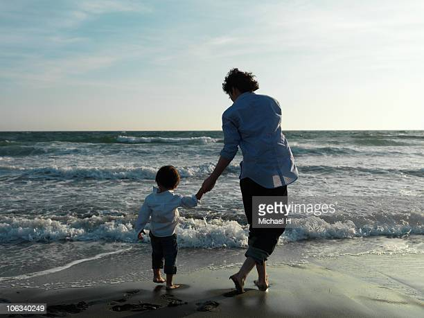 parent and child who plays in beach in evening - シングルファザー ストックフォトと画像