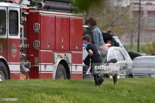 A parent and her child leave at the scene of a shooting in which at least seven students were injured at the STEM School Highlands Ranch on May 7...