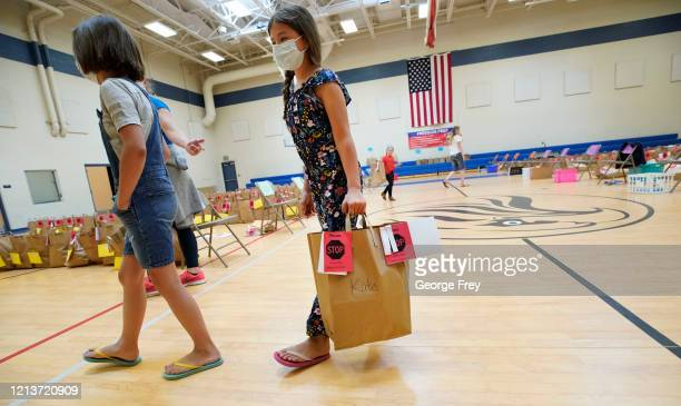 Parent and her children pick up their personal belongings that have been put in a paper bag in the gym at Freedom Preparatory Academy on May 18, 2020...