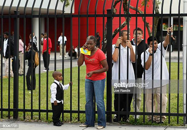A parent and students stand near the front gate to Miami Edison Senior High School after a melee broke out in the campus courtyard February 29 2008...