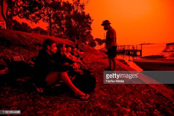 A parent assures their children that fires are not headed towards the town as the skies above turn red during the day on January 4 2020 in Mallacoota...