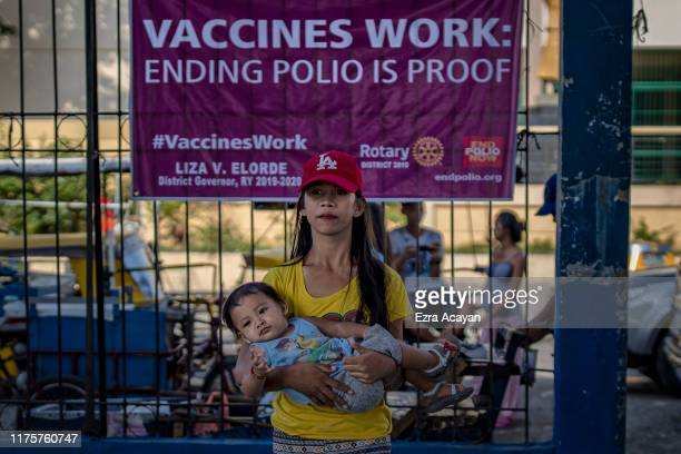 A parent brings her child to be administered an oral polio vaccine during a mass vaccination campaign to combat the resurgence of the polio virus at...