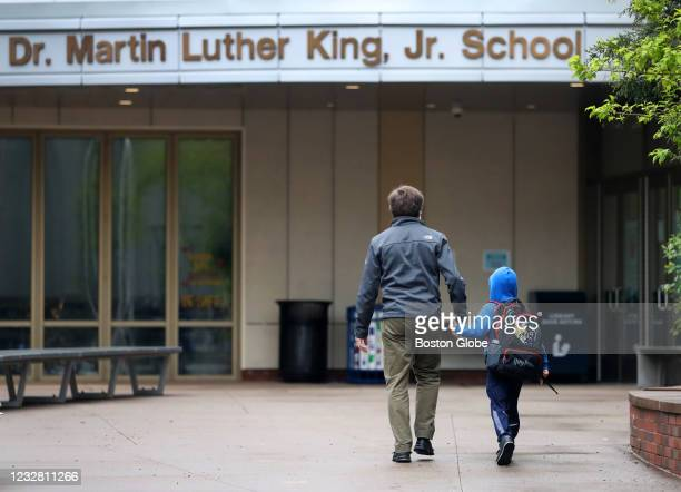 Parent brings his child to the Dr. Martin Luther King Jr. Elementary school in Cambridge, MA on April 28, 2021. Middle schools will reopen for...