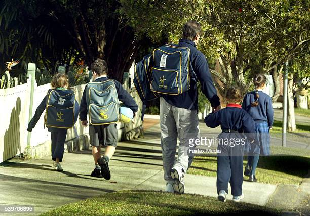 A parent escorts a group of children home from Sacred Heart Primary School in Mosman following the recent attempted abduction of one of the school's...