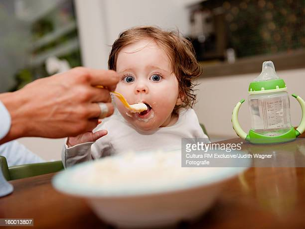 Parent feeding baby girl at table