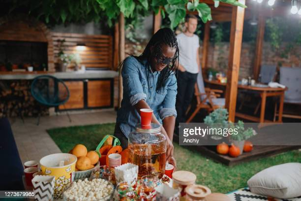 parent filling juice for her kids and their friends at backyard movie night - scaredastronaut stock pictures, royalty-free photos & images