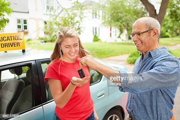 parent handing car key to young student driver horizontal - passing giving stock photos and pictures