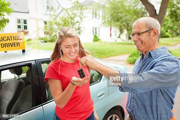 Parent Handing Car Key to Young Student Driver Horizontal