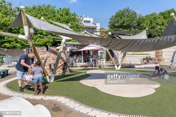 parent helping child on a swing at a children's park in melville - gazebo foto e immagini stock