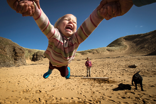 Parent holding daughter's hands, spinning her around, young son in background, low angle view, Lahinch, Clare, Ireland - gettyimageskorea