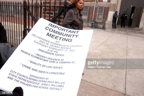 A parent holds a flyer announcing a community meeting to discuss violence in their neighborhood outside Pierce Elementary School a day after a boy...
